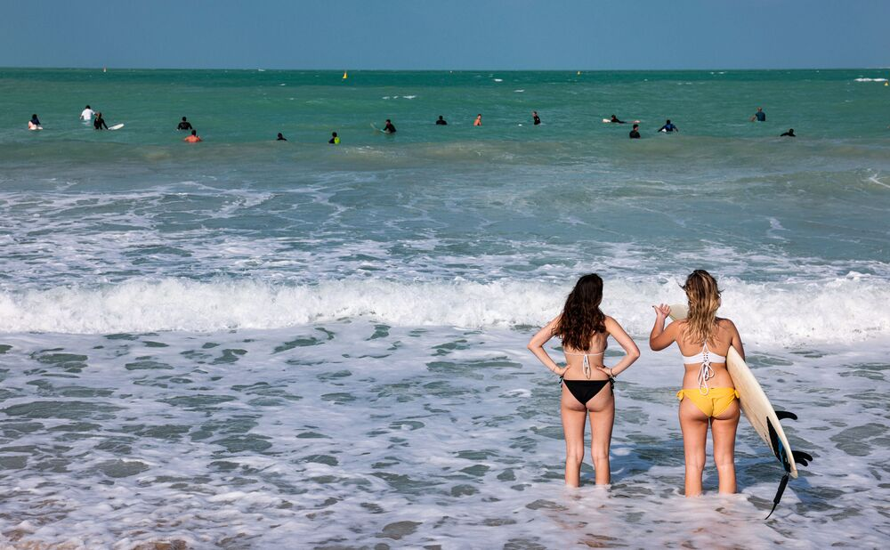 Two people survey the surf close to the shore at a beach by the Burj al-Arab hotel in Dubai on 24 November 2020.