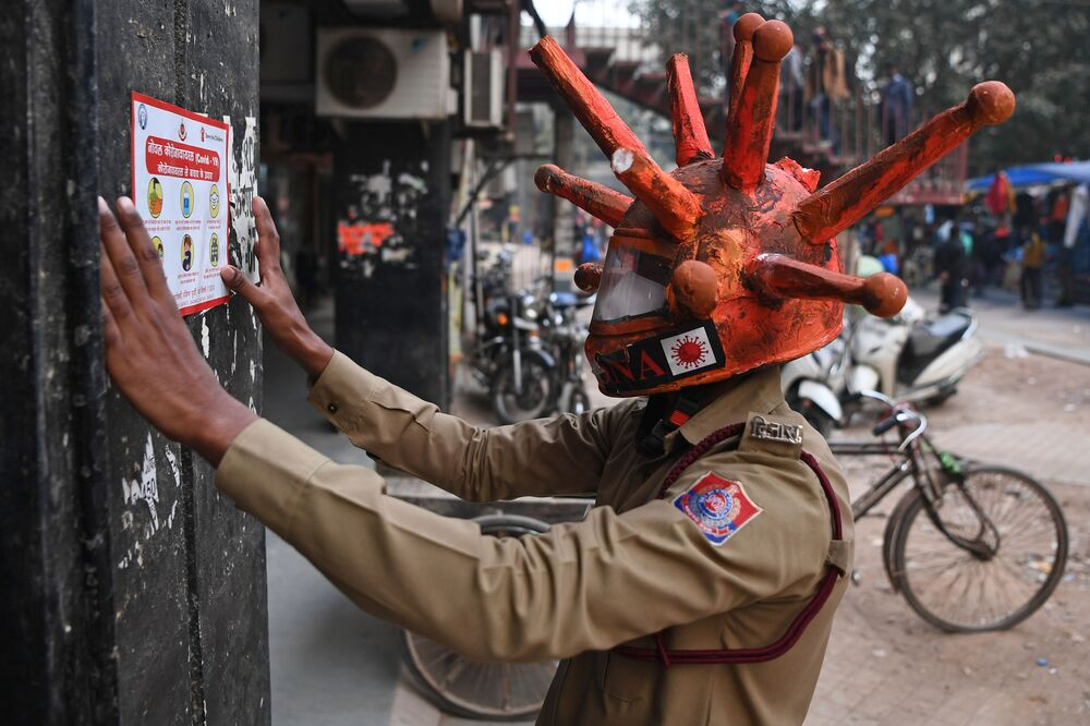 A civil defence volunteer wearing a COVID-19 coronavirus-themed helmet pastes a placard on the wall as he takes part in an awareness campaign at a market in New Delhi on 25 November 2020.