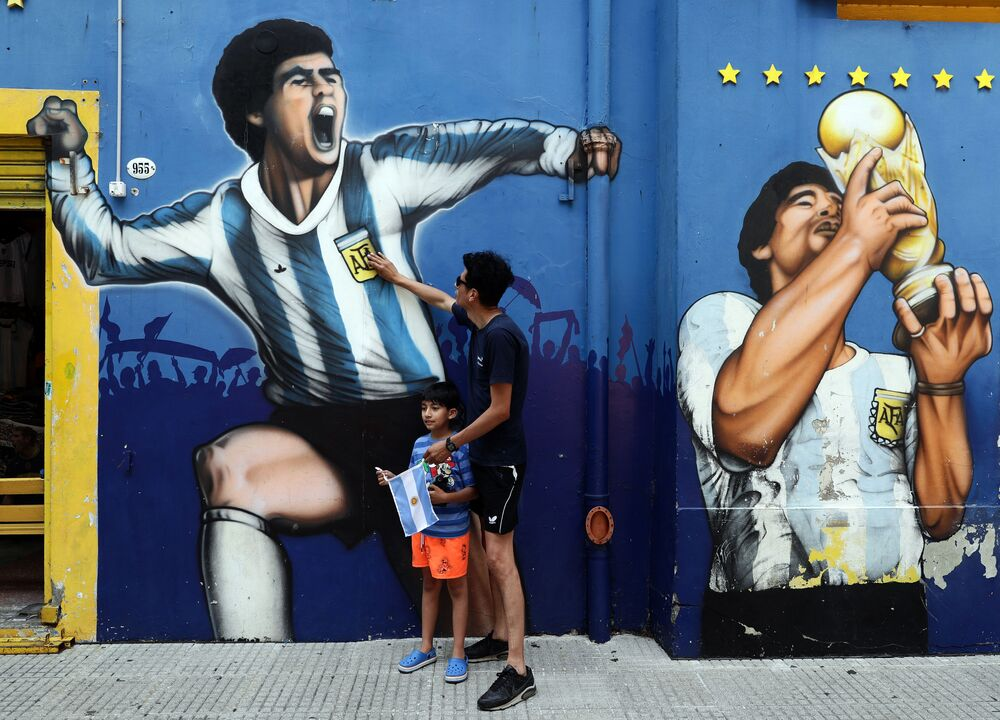 A man and his child pay tribute next to a mural depicting Argentine football legend Diego Maradona in Buenos Aires' La Boca neighbourhood on 25 November, 2020, on the day of his death.