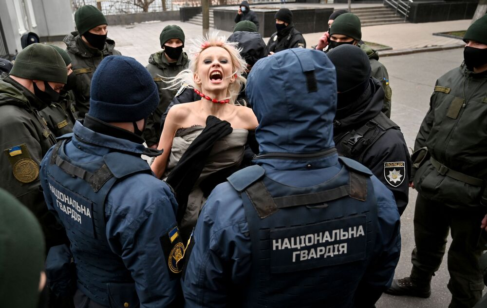Police officers arrest an activist from the Femen movement protesting outside the Ukrainian president's office to mark the International Day for the Elimination of Violence against Women in Kyiv on 25 November 2020.