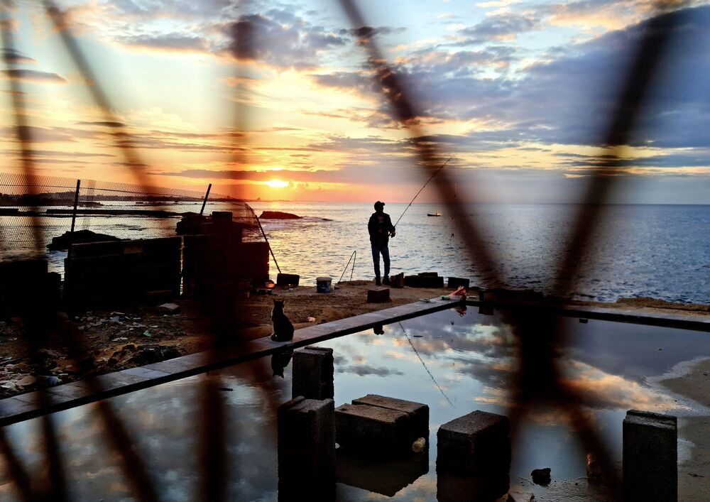 A fisherman is pictured along the promenade in Libya's capital Tripoli on 25 November 2020.