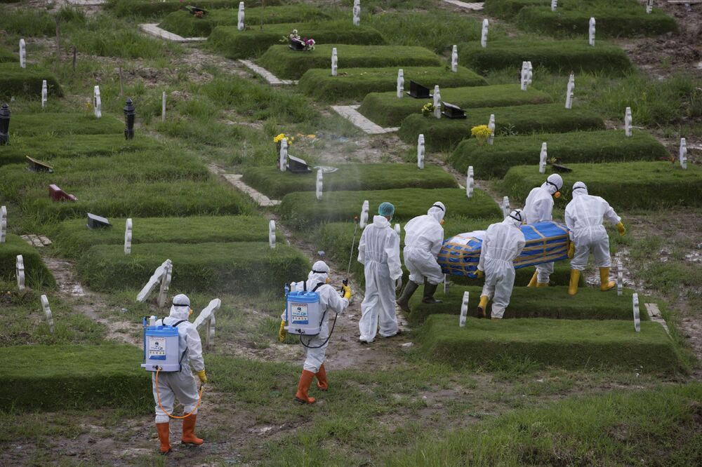 Workers in protective suits carry a coffin containing the body of someone who presumably died of the coronavirus for burial in Medan, North Sumatra, Indonesia, Tuesday, 24 November 2020.