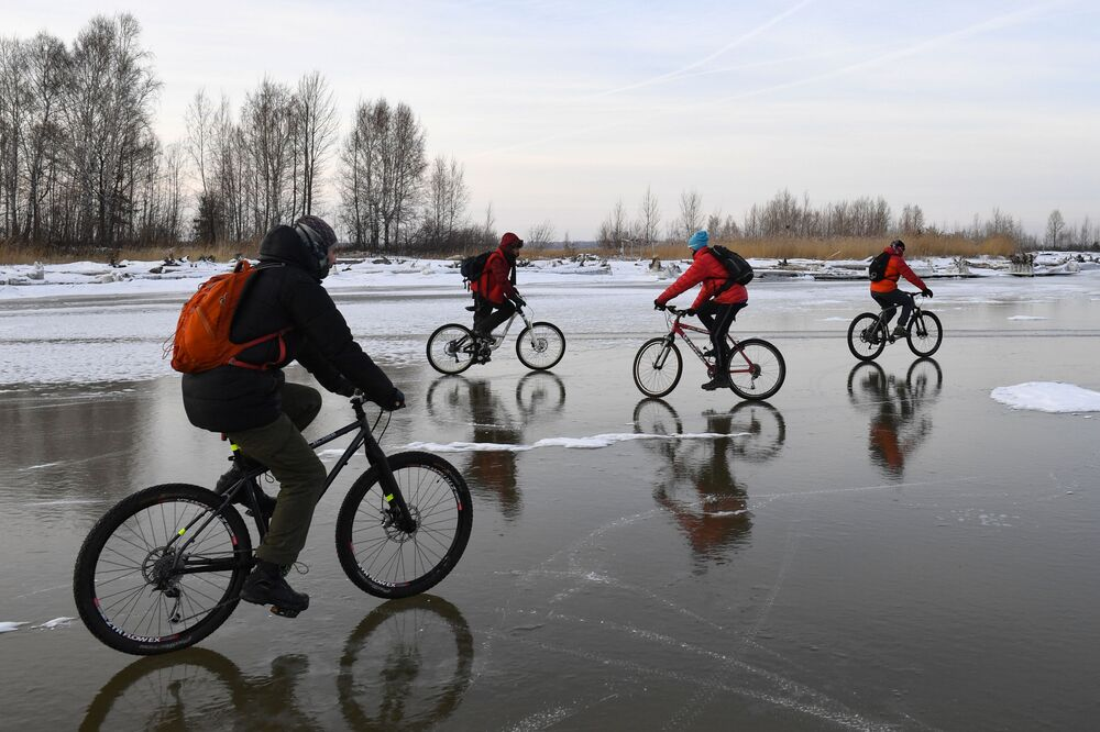 Cyclists ride on the ice of the Novosibirsk Hydroelectric Power Station reservoir near Tan-Van Island.