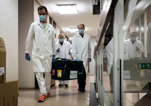 In this handout photo released by the Hungarian Foreign Ministry, laboratory assistants carry a bag with Russia's coronavirus vaccine Gam-COVID-Vac, trade-named Sputnik V inside, in Budapest, Hungary.