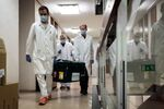 In this handout photo released by Hungarian Foreign Ministry, laboratory assistants carry a bag with Russia's coronavirus vaccine Gam-COVID-Vac, trade-named Sputnik V inside, in Budapest, Hungary