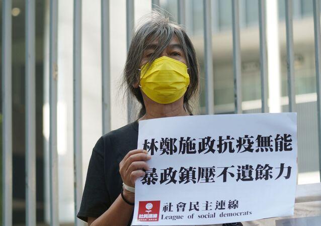 Activist Long Hair Leung Kwok-hung holds a protest sign ahead of Hong Kong Chief Executive Carrie Lam's annual policy address at the Legislative Council in Hong Kong, China November 25, 2020