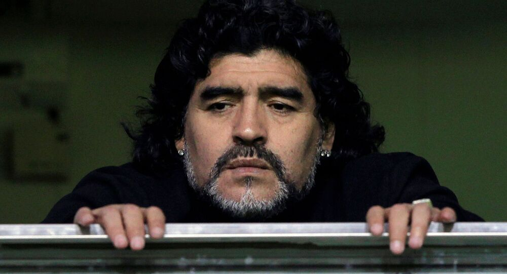 Former Argentine soccer star Diego Maradona watches from a balcony the Argentine first division soccer match between Boca Juniors and Banfield in Buenos Aires June 12, 2011.