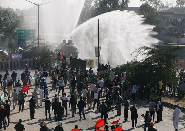 Police officers use water cannon to disperse farmers protesting against the newly passed farm bills at Singhu border near Delhi, India