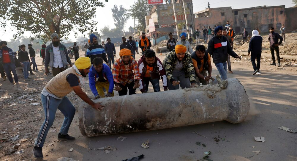 Farmers push a cement pipe to use it as a roadblock during a protest against the newly passed farm bills at Singhu border near Delhi