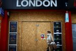 A woman walks past a boarded up London shop, amid the outbreak of the coronavirus disease (COVID-19), at Oxford Street, in London, Britain, October 14, 2020.