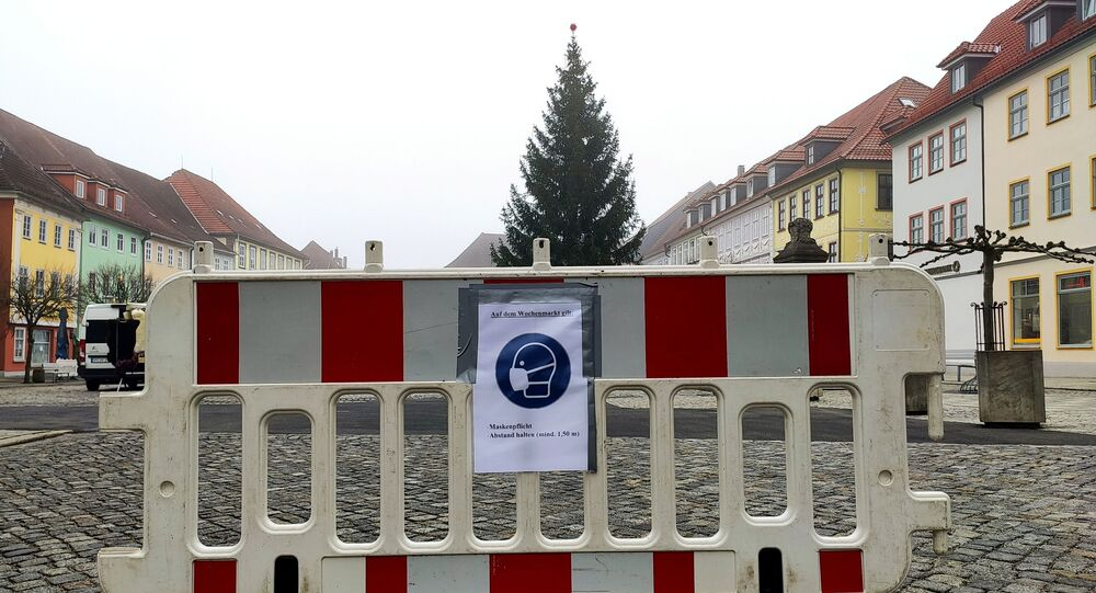 A placard reminds people to wear a protective mask and keep distance at the weekly market, as the spread of the coronavirus disease (COVID-19) continues in Hildburghausen, Germany, November 26, 2020. The state premier of Thuringia on Thursday announced a first mass test for children and teenagers in the district of Hildburghausen, Germany's coronavirus hotspot, to find out to what extent they contribute to a rapid surge in infections.