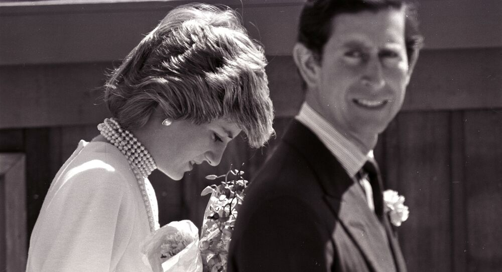 Princess Diana bows her head following Prince Charles on a walk to the California Pavilion in Vancouver May 6, 1986