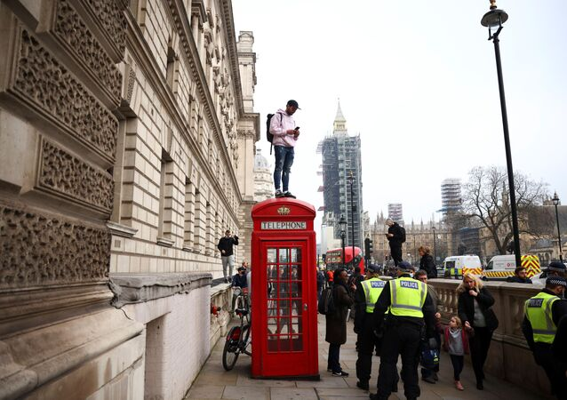 A man stands on a telephone booth during an anti-lockdown demonstration amid the coronavirus disease (COVID-19) outbreak in London, Britain November 28, 2020.