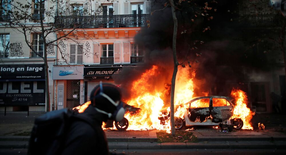 Cars burn during a demonstration against the Global Security Bill that rights groups say would make it a crime to circulate an image of a police officer's face and would infringe journalists' freedom in France, in Paris, November 28, 2020.
