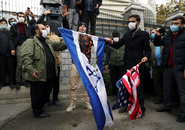 Protesters burn the U.S. and Israeli flags during a demonstration against the the killing of Mohsen Fakhrizadeh, Iran's top nuclear scientist, in Tehran, Iran, November 28, 2020.