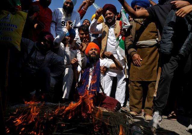 Farmers shout slogans after burning an effigy during a protest against the newly passed farm bills at Singhu border near Delhi, India, November 28, 2020.