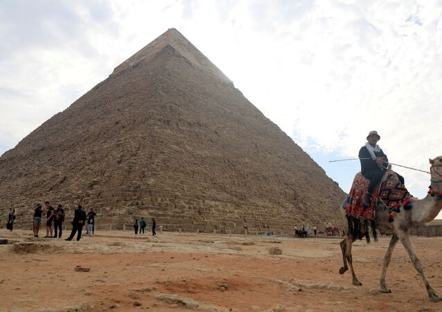 A camel guide waits for customers next to the pyramid of Khafre or Chefren at the Giza pyramids plateau in Giza, Egypt, 15 November 2020