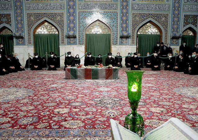 Servants of the holy shrine of Imam Reza sit near the coffin of Iranian nuclear scientist Mohsen Fakhrizadeh, in Mashhad, Iran November 29, 2020.