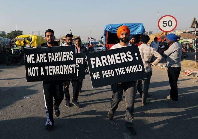 Farmers carry placards at a site of a protest against the newly passed farm bills at Singhu border near Delhi, India, November 28, 2020