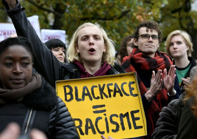 A man holds a sign as he protests against the arrival of Saint Nicholas and his assistants called Zwarte Piet (Black Pete) in The Hague, Netherlands, November 16, 2019. The sign reads Blackface is racism.