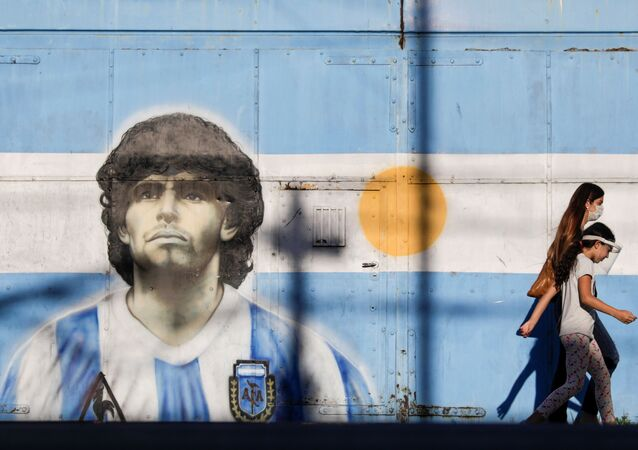 People walk past graffiti featuring soccer legend Diego Armando Maradona in Buenos Aires, Argentina, 27 November 2020