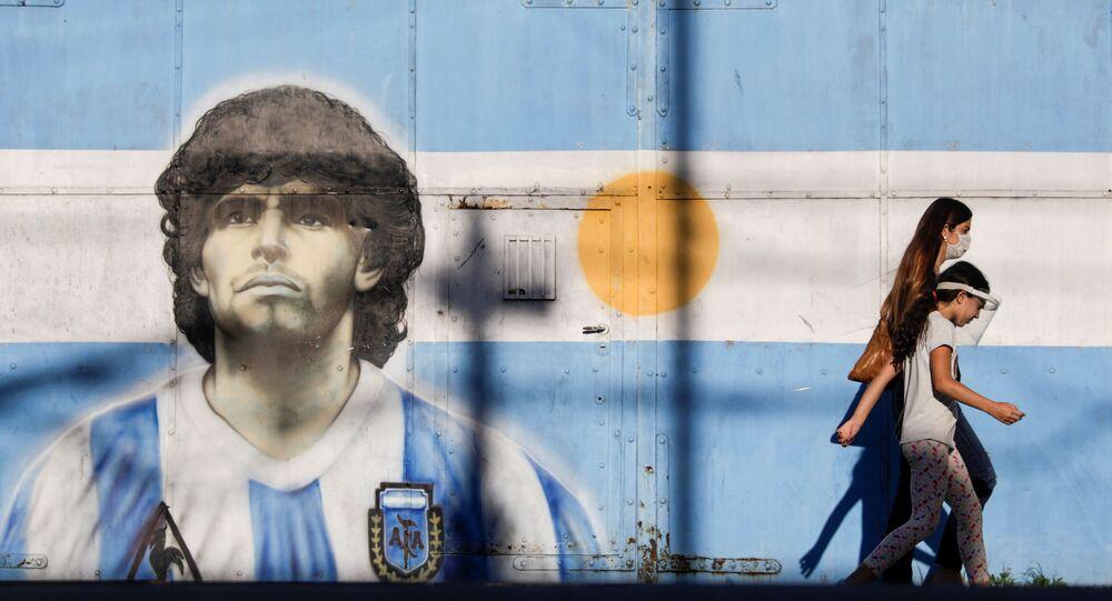 People walk past graffiti of soccer legend Diego Armando Maradona in Buenos Aires, Argentina, 27 November 2020.