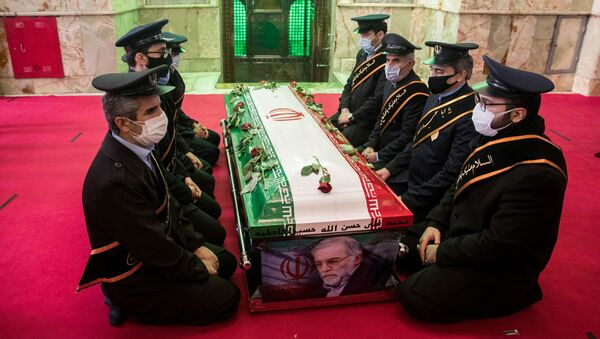 Mourners sit next to the coffin of Iranian nuclear scientist Mohsen Fakhrizadeh, during the burial ceremony at the shrine of Imamzadeh Saleh, in Tehran, Iran November 30, 2020. - Sputnik International