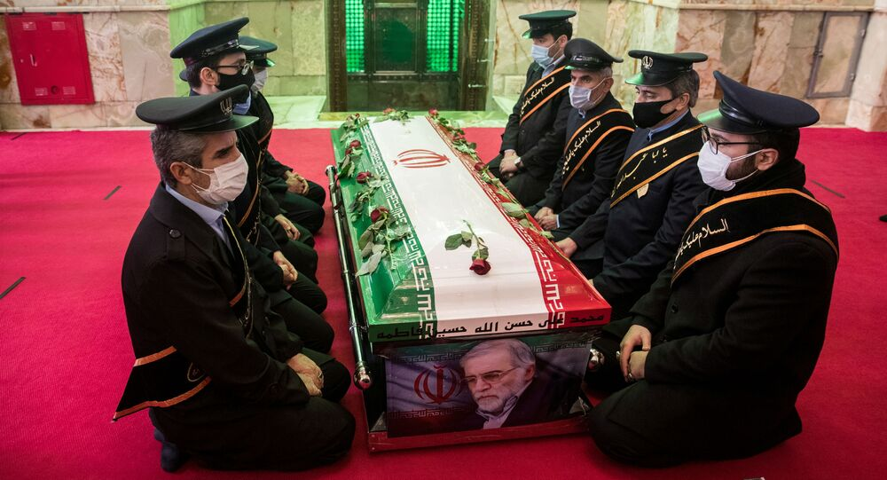 Mourners sit next to the coffin of Iranian nuclear scientist Mohsen Fakhrizadeh, during the burial ceremony at the shrine of Imamzadeh Saleh, in Tehran, Iran November 30, 2020.