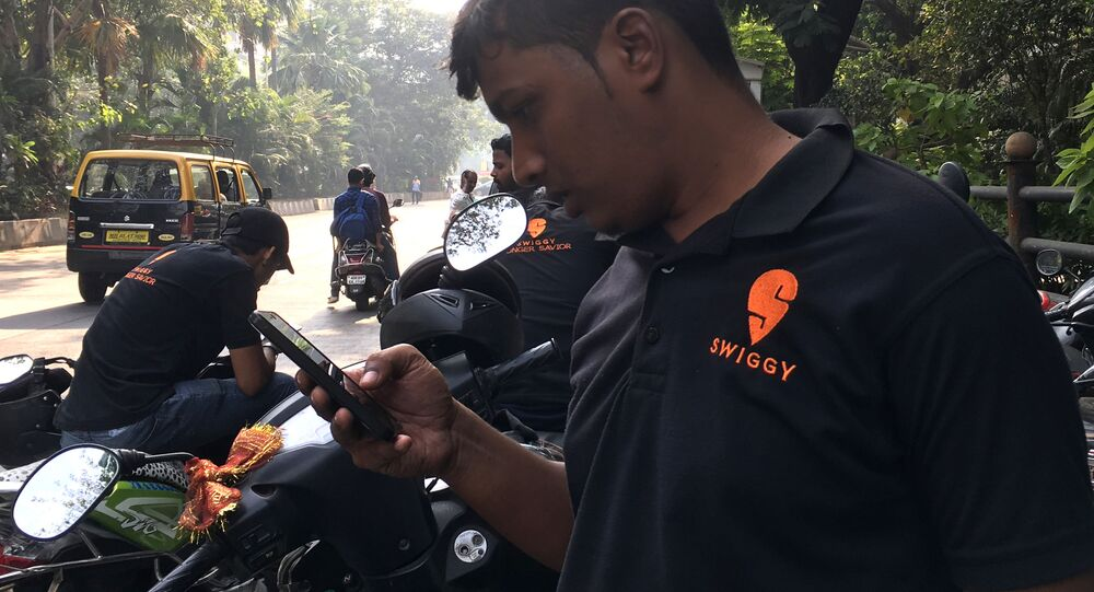 In this photograph taken on December 24, 2018, an Indian delivery man working with the food delivery app Swiggy checks his phone in a business district in Mumbai