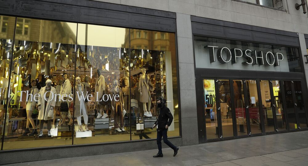 A person wearing a face mask to try to curb the spread of coronavirus walks past the temporarily closed Topshop flagship store on Oxford Street, during England's second coronavirus lockdown, in London, Monday, Nov. 30, 2020. Arcadia Group, the retail empire of tycoon Philip Green, which owns well-known British fashion chains like Topshop