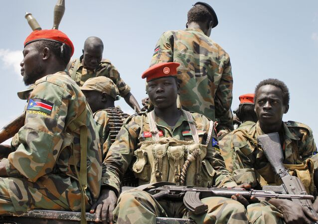In this photo taken Sunday, Oct. 16, 2016, a group of South Sudanese government soldiers sit on the back of a pickup truck before visiting the scene of a recent battle in Malakal, South Sudan