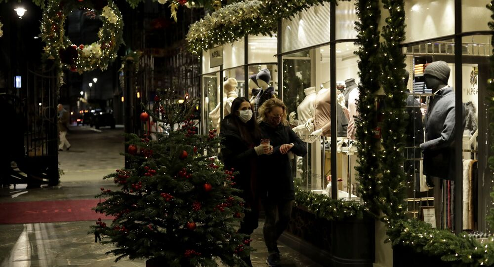 Women wearing face masks walk past a Christmas tree and lights in Burlington Arcade, where all non-essential shops are temporarily closed during England's second coronavirus lockdown, in London, Wednesday, Nov. 25, 2020