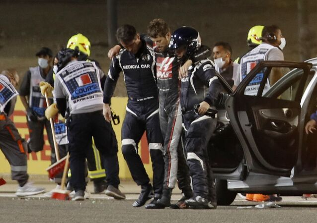 Formula One F1 - Bahrain Grand Prix - Bahrain International Circuit, Sakhir, Bahrain - November 29, 2020 Haas' Romain Grosjean walks away from the crash scene with the help of medical officers after crashing out of the race. Pool via REUTERS/Hamad I Mohammed