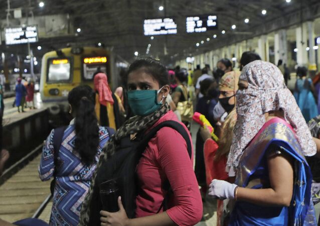 Women passengers wait for a local train in Mumbai, India, Wednesday, Oct. 21, 2020