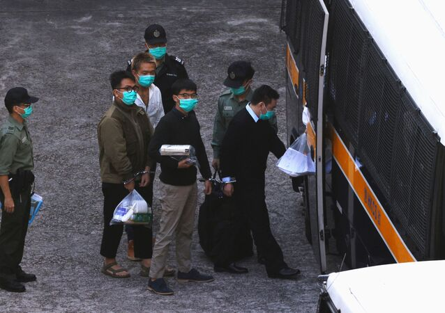 Pro-democracy activists Ivan Lam and Joshua Wong walk to a prison van to head to court, after pleading guilty to charges of organising and inciting an unauthorised assembly near the police headquarters during last year's anti-government protests, in Hong Kong, China December 2, 2020
