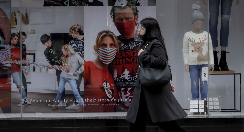 A woman wearing a face shield walks past the front window of the Primark clothing store on Oxford Street during England's second coronavirus lockdown, in London, Monday, Nov. 23, 2020