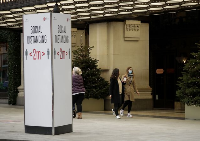 A woman wearing a face mask walks past Christmas trees and a social distancing sign outside the Selfridges department store on Oxford Street, which is temporarily closed for in-store browsing with online collection possible from a collection point, during England's second coronavirus lockdown, in London, Monday, Nov. 23, 2020