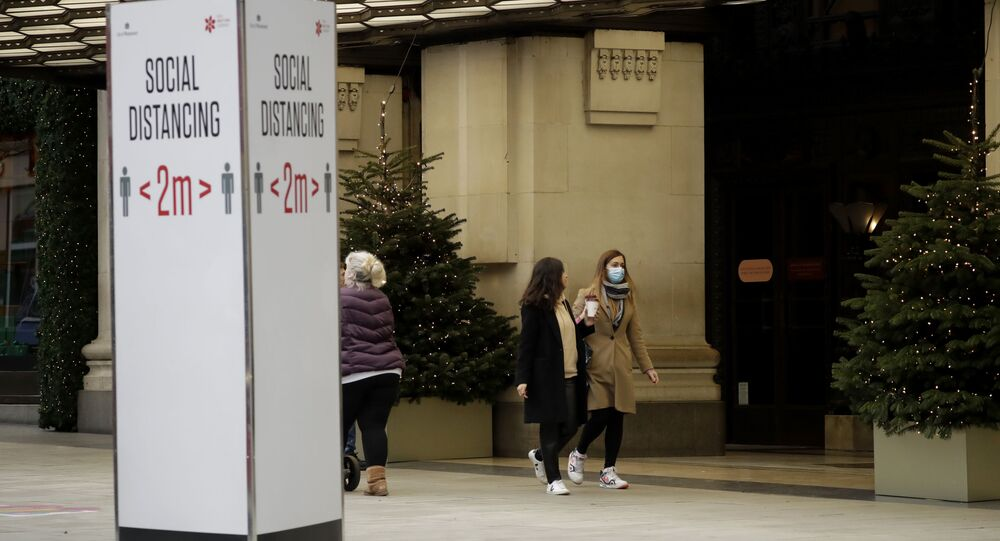 A woman wearing a face mask walks past Christmas trees and a social distancing sign outside Selfridges department store in Oxford Street, which was closed down for most of November, offering only online shopping and collection from a specific point. 23 November 2020.