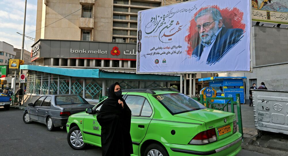 A woman walk by a billboard in honour of slain nuclear scientist Mohsen Fakhrizadeh in the Iranian capital Tehran, on November 30, 2020