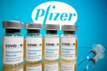 Vials with a sticker reading, COVID-19 / Coronavirus vaccine / Injection only and a medical syringe are seen in front of a displayed Pfizer logo in this illustration taken October 31, 2020