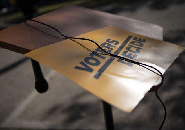 A sign that reads Voters Decide is placed next to a hanging microphone as people gather at the Civic Center Park while waiting for the results of election, Wednesday, Nov. 4, 2020, in Kenosha, Wis.