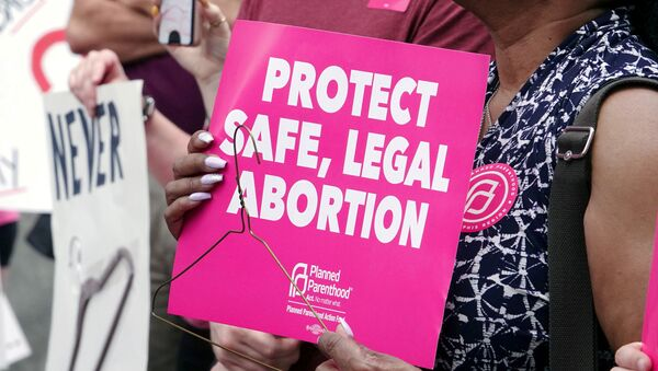 An abortion rights activist holds a sign in downtown Memphis during a Stop Abortion Bans Day of Action rally hosted by the Tennessee chapter of Planned Parenthood in Tennessee, U.S., May 21, 2019 - Sputnik International