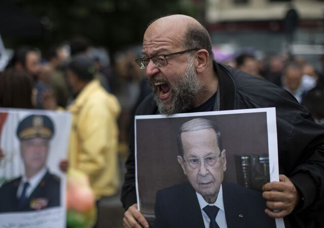 An anti-government protester holds a picture of Lebanese President Michel Aoun as he shouts slogans during a protest, in Beirut's Ashrafieh district, Lebanon, Thursday, Nov. 26, 2020.