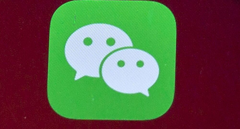 Icons for the smartphone apps WeChat are seen on a smartphone screen in Beijing, on Aug. 7, 2020.  The Justice Department is asking a judge to allow WeChat to be banned from app stores in the U.S., pending an appeal. In a Friday, Sept. 25, 2020 filing, the Justice Department requested U.S. Magistrate Judge Laurel Beeler in California put on hold a preliminary injunction issued Saturday.