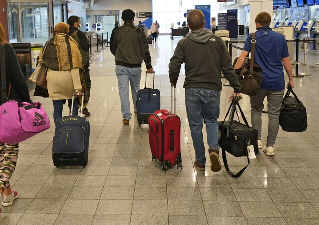 Travelers walk through the terminal at Cleveland Hopkins International Airport before boarding a plane, Wednesday, Nov. 25, 2020, in Cleveland.