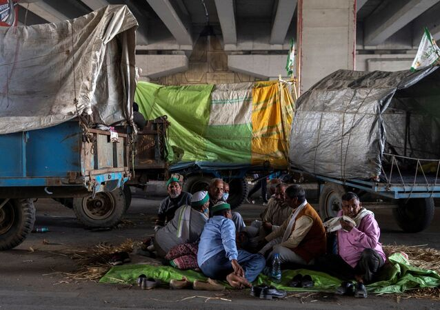Farmers rest near their parked tractor trolleys at the site of a protest against the newly passed farm bills at the Delhi-Uttar Pradesh border in Ghaziabad, India