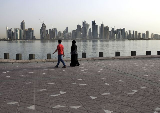 In this Friday, May 4, 2018, photo, a couple walk by the sea with the city skyline in the background, in Doha, Qatar