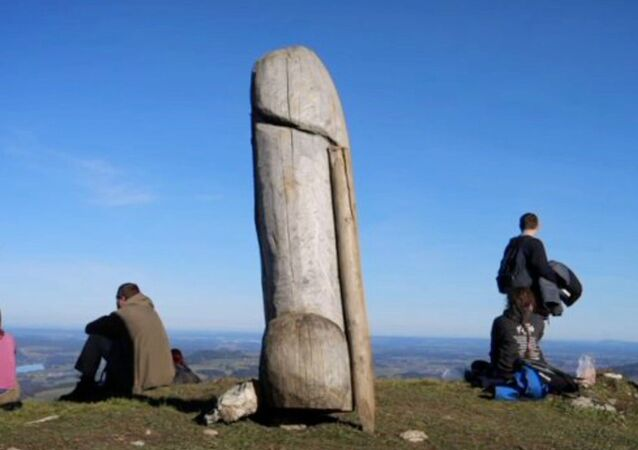 Screenshot captures the original wooden phallus statue that previously sat on the Grünten mountain, which is located in the German state of Bavaria. The statue went mysteriously missing  and has since been replaced by a similar, but larger structure.