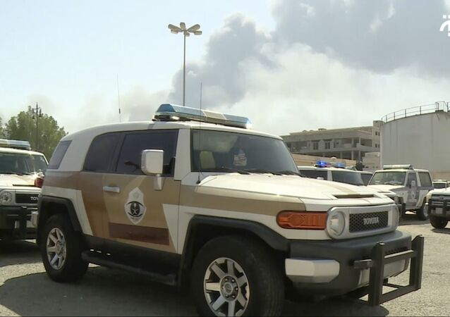 In this image made from a video broadcast on the Saudi-owned Al-Arabiya satellite news channel on Saturday, Sept. 14, 2019, a Saudi police cruiser sits in a parking lot as the smoke from a fire at the Abqaiq oil processing facility can be seen behind it in Buqyaq, Saudi Arabia