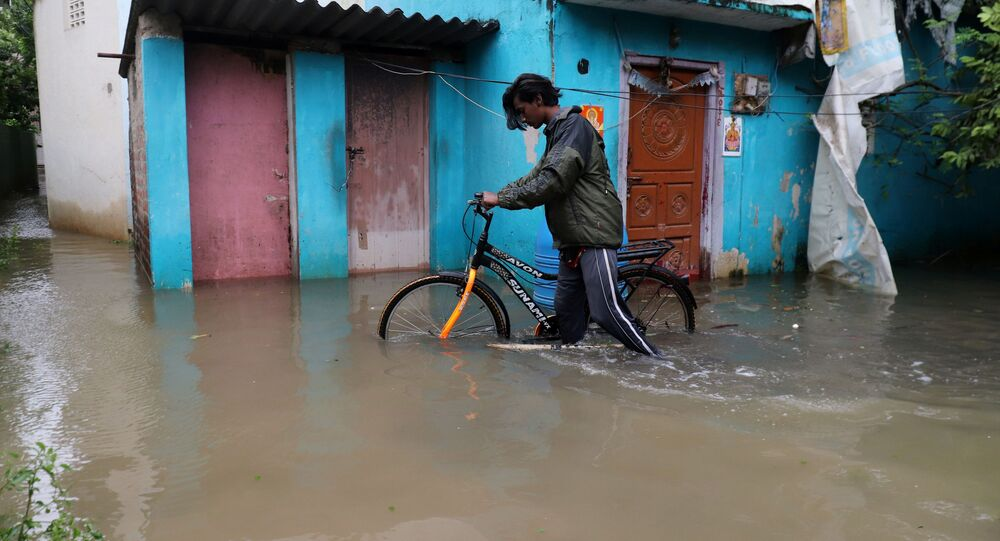 A man pushes his bicycle through a water-logged neighbourhood after Cyclone Nivar's landfall, in Chennai, India